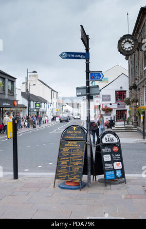 Main Street, the town centre of Keswick, Cumbria, uk with busy shoppers and lots of activity on a cloudy, summer afternoon. - Stock Photo
