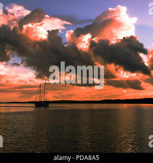 Summer sunset with predominately cumulonimbus clouds against a steel blue sky reflected in ocean water. Fraser Island, Queensland, Australia. - Stock Photo