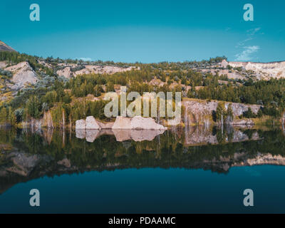 Aerial drone photo of beautiful shore reflecting in water,view inside abandoned quarry, the slopes overgrown of mixed forest, stones that fall into th - Stock Photo