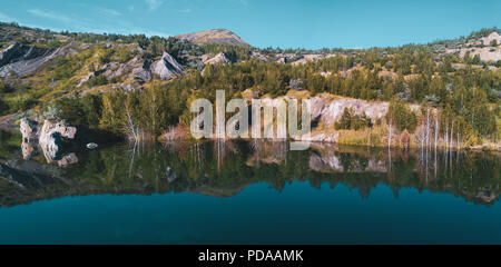Aerial drone photo of beautiful shore reflecting in water,view inside abandoned quarry, the slopes overgrown of mixed forest, Russia - Stock Photo