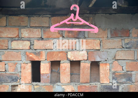 Rack with hanging clothes against brick wall, closeup Stock