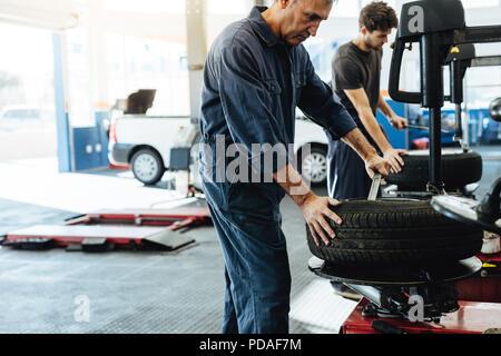Mechanics working in car repair workshop. Auto repair workers working on tire replacing machine in auto repair shop. - Stock Photo