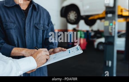 Mechanic taking sign on document from customer in garage. Hands of car service client signing papers after getting his car repaired. - Stock Photo