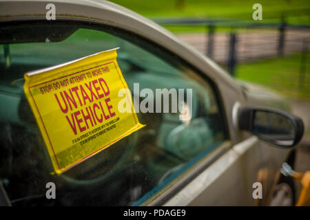 Detail Of A Warning Sign On The Window Of An Untaxed Vehicle With A Clamp On The Front Wheel - Stock Photo