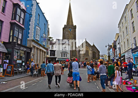 Holidaymakers throng the central streets of the pretty seaside resort of Tenby, Wales, on a dull summers day in 2018. St Marys church is to the rear. - Stock Photo