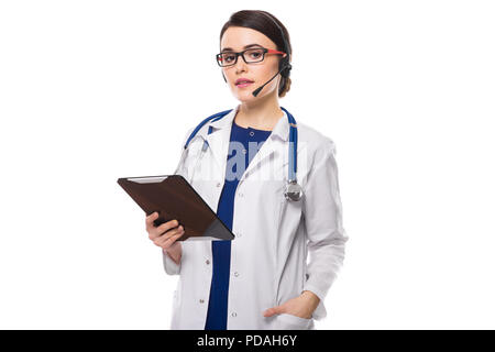 Young woman doctor with stethoscope and headphones holding tablet in her hands in white uniform on white background - Stock Photo