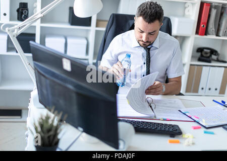 A man is sitting at a table in the office, working with documents and holding a bottle of water in his hand. - Stock Photo