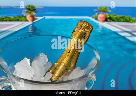 LUXURY VACATION Champagne bottle on ice, chilling in crystal glass wine cooler on terrace with luxury vacation infinity pool and sea coast view behind - Stock Photo