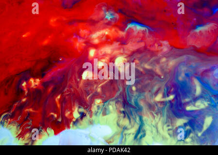 Abstract liquid milk flowing pattern like nebulae in the universe with different colours of white, blue, red and pink - Stock Photo