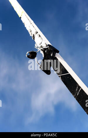 Single new cross-country ski set against a blue winter sky with defocused clouds in the background with a copy space area for wintery themed sports an - Stock Photo