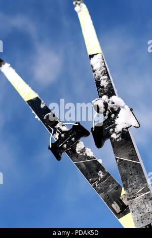 Pair of new cross-country skis set against a blue winter sky with defocused clouds in the background with a copy space area for wintery themed sports  - Stock Photo