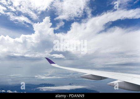 Plane wing flying over white clouds and ocean. - Stock Photo