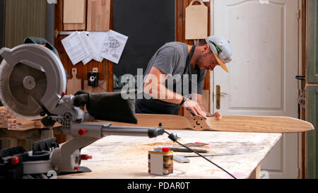 Experienced carpenter in work clothes and small buiness owner working in woodwork workshop,  using sandpaper for polishing children's helicopter blade - Stock Photo