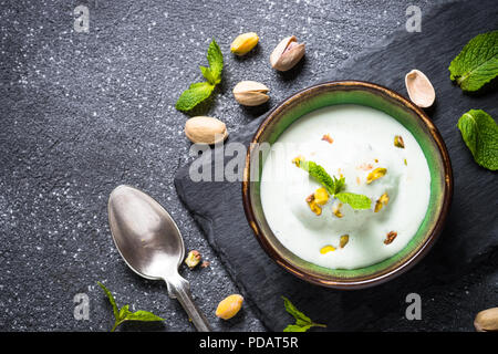 Pistachios ice cream in bowls on black stone table. - Stock Photo