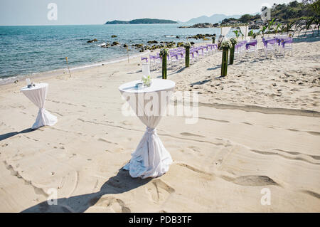 White cloth decorating snack, glasses table, beach wedding venue at seaside with panoramic ocean view - Stock Photo