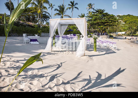 Beach wedding venue settings at seaside on the white sand, Arches and altar decoratiing with white soft fabric on the bamboo frame, white chiavari cha - Stock Photo