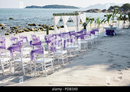 Beach wedding venue settings on the white sand at seaside with white chiavari chairs decorating with violet organza sash, minimal flower decoration, p - Stock Photo