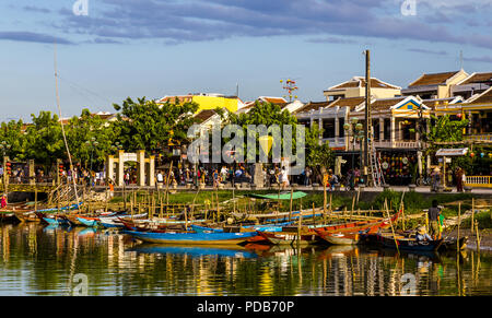 Many boats lined up along the river front by people walking in front of the shops. - Stock Photo
