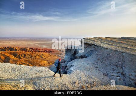 Tourist walking at the on surreal white mountains in desert park Altyn Emel in Kazakhstan - Stock Photo