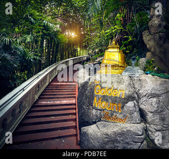 Golden Stupa statue in the tropical jungle near the stairs in Wat Saket Golden Mountain Temple famous Landmark in Bangkok, Thailand - Stock Photo