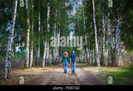 Happy couple in checked shirts on the road in birch wood in Kyrgyzstan. Romantic date in the forest. - Stock Photo
