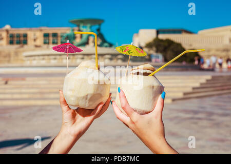 Women holding up coconut drinks in Valletta, Malta - Stock Photo