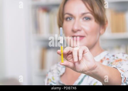 Woman is holding syringe with insulin or heparin in her hand at home - Stock Photo