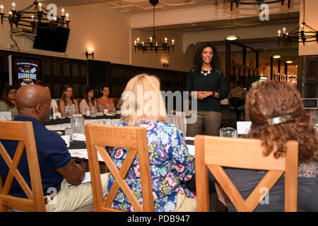 Tonya Wright, spouse of Chief Master Sgt. of the Air Force Kaleth O. Wright, speaks with Team Mildenhall spouses during a breakfast at the Gateway Dining Facility at RAF Mildenhall, England, Aug. 2, 2018. Mrs. Wright met with Team Mildenhall spouses, where she answered questions and listened to their perspectives as military spouses. (U.S. Air Force photo by Senior Airman Christine Groening) - Stock Photo