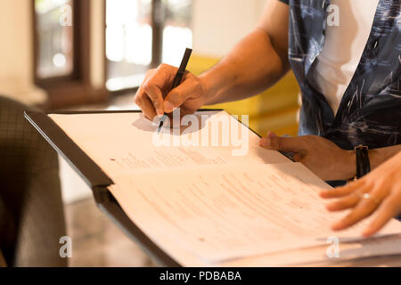 Mans hand signing agreement from for hotel reservation - Stock Photo