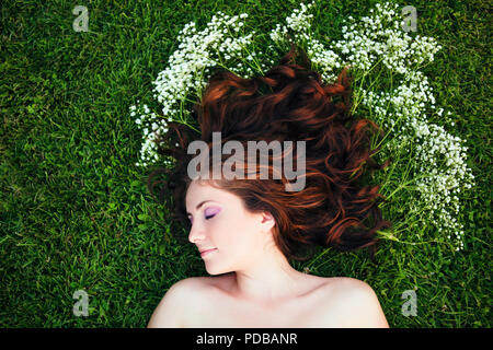 Closeup portrait of young beautiful girl woman with red brown hair lying on grass with white small flowers around her head. View from above top overhe - Stock Photo