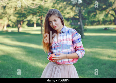 Portrait of beautiful young Caucasian woman with long red hair in plaid shirt and pink tutu tulle skirt,  in park meadow at summer sunset, looking in  - Stock Photo