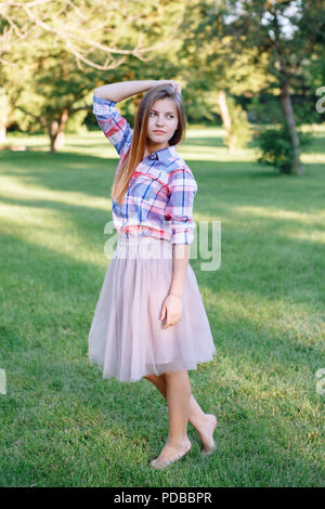 Portrait of beautiful young Caucasian woman with long red hair in plaid shirt and pink tutu tulle skirt, standing posing barefoot on toes on grass in  - Stock Photo