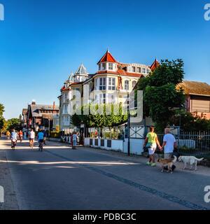 Bansin Beach promenade and holiday houses. People walking at Baltic sea holiday resort on Usedom Island Heringsdorf, Germany - Stock Photo