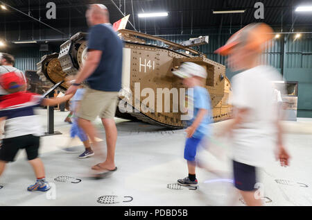 People make their way past a World War One MkV tank which saw action at the battle of Amiens with C Company, 8th Battalion, under 2nd Lieutenant Harold Whittenbury, during an event at The Tank Museum in Bovington, Dorset, to mark the 100th anniversary of the Battle of Amiens, which saw more than 500 tanks spearhead an attack which ultimately led to the end of the First World War. - Stock Photo