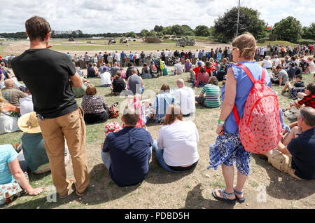 People watch a mock battle in the arena during an event at The Tank Museum in Bovington, Dorset, to mark the 100th anniversary of the Battle of Amiens, which saw more than 500 tanks spearhead an attack which ultimately led to the end of the First World War. - Stock Photo