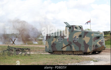 A replica World War One A7V tank takes part in a mock battle during an event at The Tank Museum in Bovington, Dorset, to mark the 100th anniversary of the Battle of Amiens, which saw more than 500 tanks spearhead an attack which ultimately led to the end of the First World War. - Stock Photo