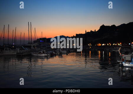 Bright Orange Sunset Reflecting in the Sea Over Baska Voda Harbour Croatia with Silhouetted Yachts and Boats - Stock Photo