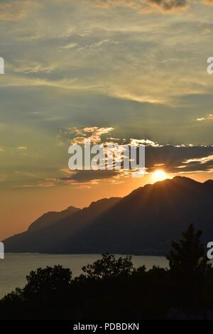 Bright Orange Sunset Silhouetting the Mountains of the Dalmatian Coast Croatia with Sunlight Beaming through the Clouds - Stock Photo