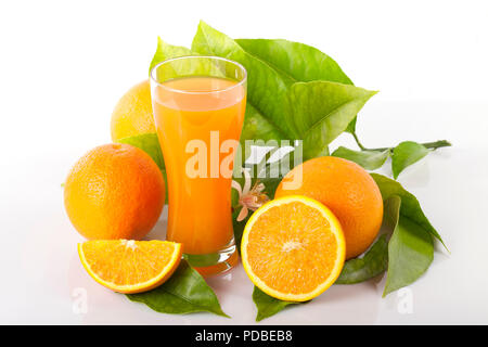 Oranges and orange tree leaves next to a glass full of orange juice isolated on white. - Stock Photo