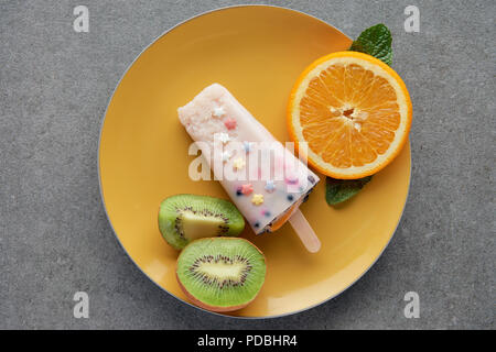 top view of delicious popsicle with slices of orange and kiwi on yellow plate on grey - Stock Photo