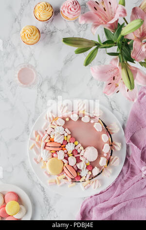 top view of sweet birthday cake with marshmallows and pink lily flowers on marble table - Stock Photo