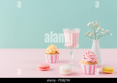 cupcakes, milkshake and macarons on birthday background with flowers - Stock Photo