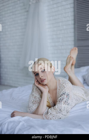 beautiful young bride in negligee on lying bed and looking at camera - Stock Photo