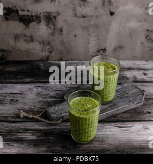 Organic green smoothie in glasses on wooden table - Stock Photo