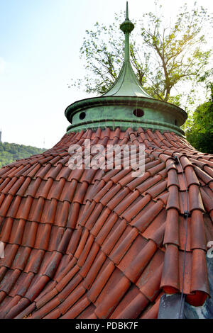 Curved tiled rotunda belvedere roof with detail of red clay roofing tiles and copper cupola on Prague Castle peripheral wall - Stock Photo