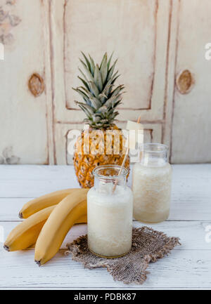 Organic fruit smoothie with bananas and pineapple on white background - Stock Photo
