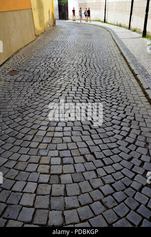 View down old narrow cobblestone paved road between buildings with pedestrians walking at end - Stock Photo