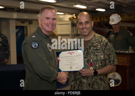 NEWPORT NEWS, Va. (Aug. 3, 2018) Capt. Matthew Kawas, from Matawan, New Jersey, USS Gerald R. Ford's (CVN 78) reactor officer, is awarded a Legion of Merit Medal by Capt. Richard McCormack, Ford's commanding officer, during an awards at quarters ceremony. (U.S. Navy photo by Mass Communication Specialist 3rd Class Joshua Murray) - Stock Photo
