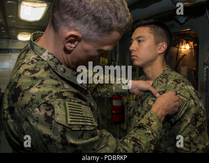 NEWPORT NEWS, Va. (Aug. 3, 2018) Cryptologic Technician (Collection) 2nd Class Benjamin Mizuo, from Everett, Washington, assigned to USS Gerald R. Ford (CVN 78), receives his Enlisted Information Warfare Specialist pin from Senior Chief Intelligence Specialist Michael Linares. (U.S. Navy photo by Mass Communication Specialist 2nd Class Cat Campbell) - Stock Photo