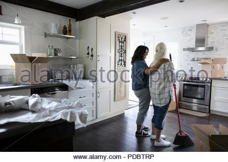 Affectionate daughter with senior mother, downsizing, packing and sweeping kitchen - Stock Photo